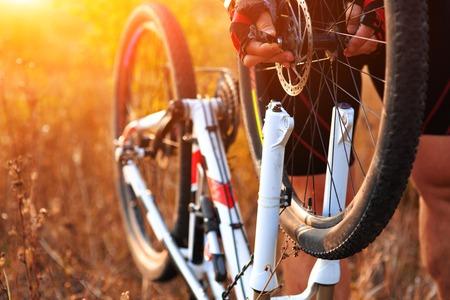 48404461 - bike repair. young man repairing mountain bike in the forest